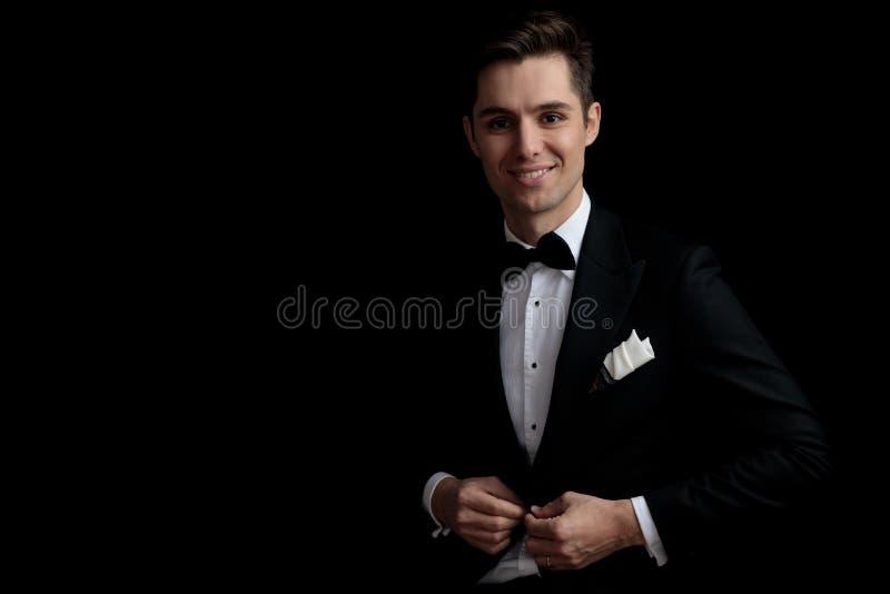 Homme heureux de mode dans le smoking noir boutonnant sa veste de salon photo stock