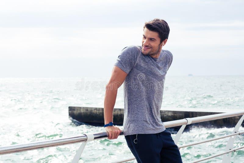 Homme heureux de sports se reposant près de la mer dehors image stock