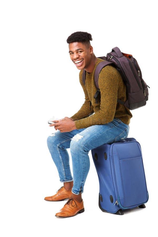 Homme heureux de voyage d'afro-américain s'asseyant sur la valise avec le téléphone portable sur le fond blanc d'isolement photo libre de droits