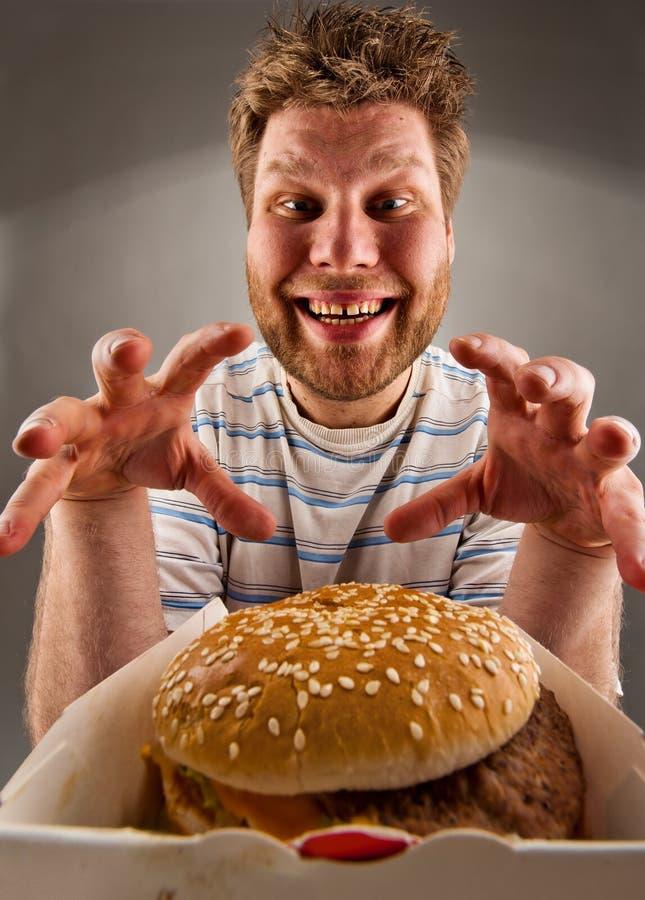 Homme heureux disposant à manger l'hamburger photos libres de droits