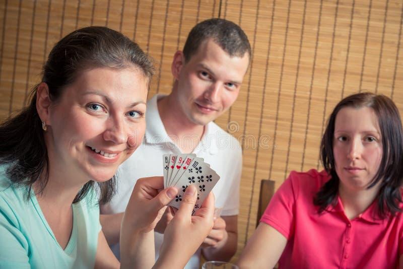 Homme heureux et deux femmes jouant le tisonnier photographie stock libre de droits