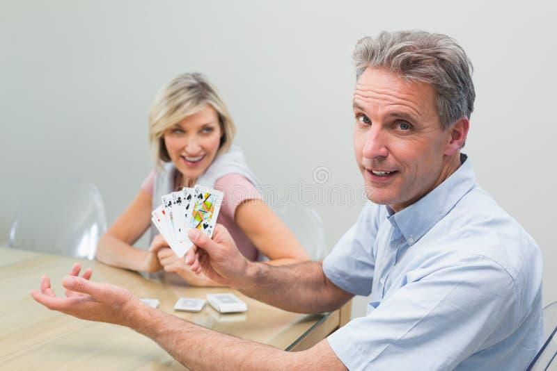 Homme heureux et femme jouant des cartes à la maison images stock