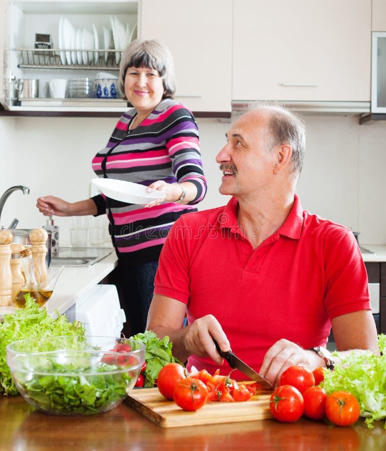 Homme heureux et femme mûre faisant les travaux domestiques ensemble photographie stock libre de droits