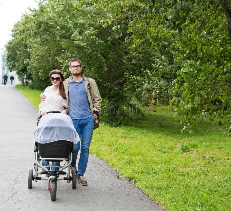 Homme heureux et femme marchant avec le landau de bébé photo stock