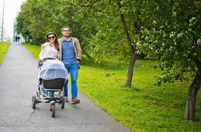 Homme heureux et femme marchant avec le landau de bébé photo libre de droits