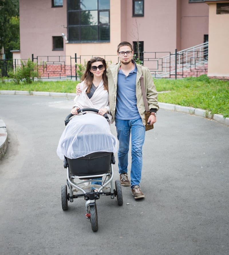 Homme heureux et femme marchant avec le landau de bébé images stock