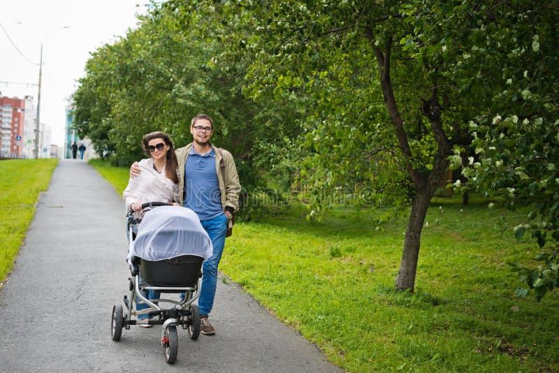 Homme heureux et femme marchant avec le landau de bébé photos libres de droits