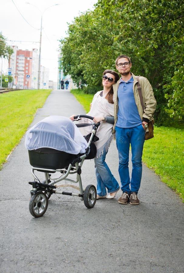 Homme heureux et femme marchant avec le landau de bébé photographie stock