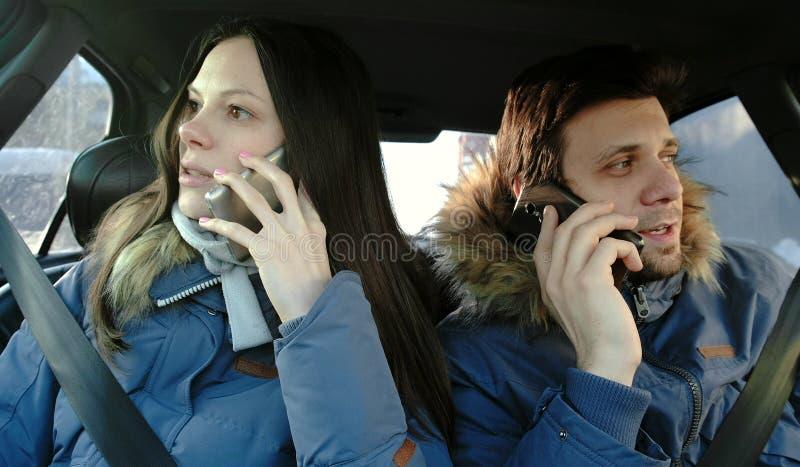 Homme heureux et femme parlant leurs téléphones portables et s'asseyant dans la voiture Front View photo stock