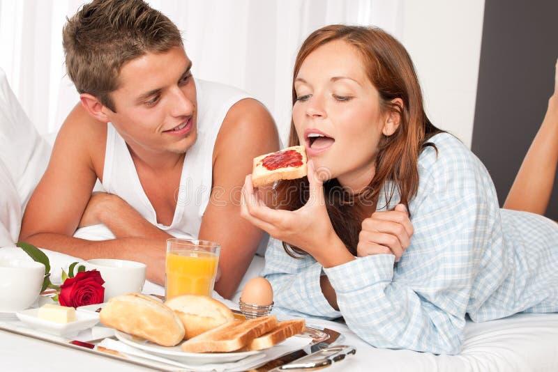 Homme heureux et femme prenant le petit déjeuner image stock