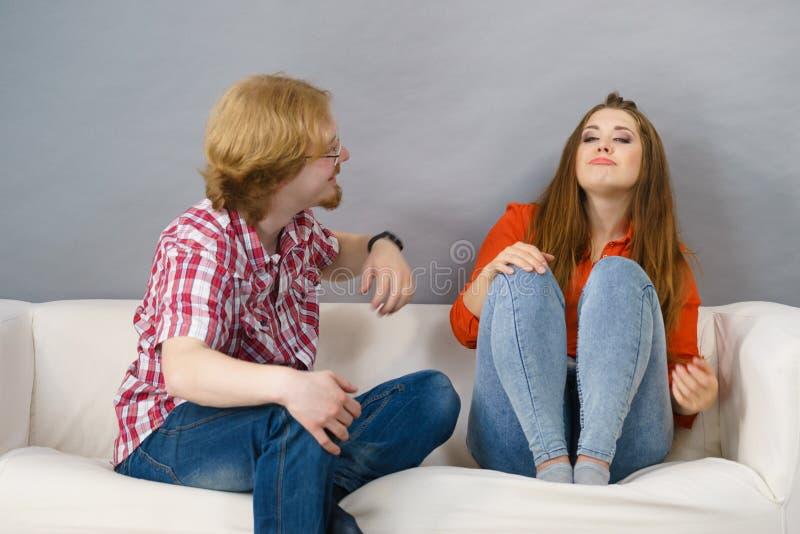Homme heureux et femme s'asseyant sur le sofa image stock