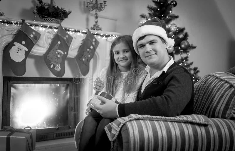 Homme heureux et fille s'asseyant à la cheminée à Noël photos stock