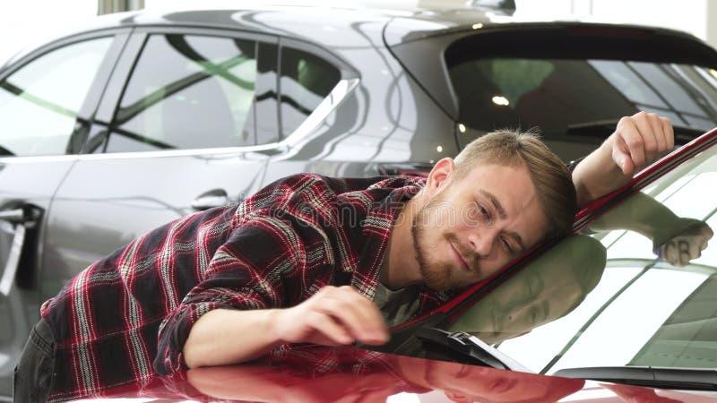 Homme heureux frottant sa nouvelle voiture souriant doucement montrant des pouces au concessionnaire photographie stock libre de droits