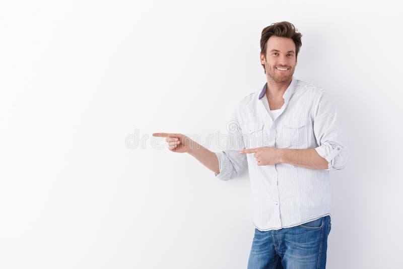 Homme heureux indiquant la droite photographie stock