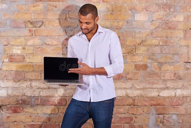 Homme heureux indiquant un ordinateur portable images stock