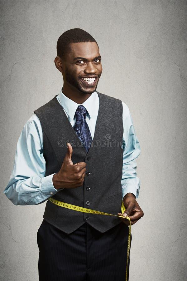 Homme heureux mesurant sa taille avec la bande photographie stock