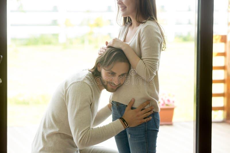 Homme heureux mettant l'oreille au ventre enceinte d'épouse à la maison photo stock