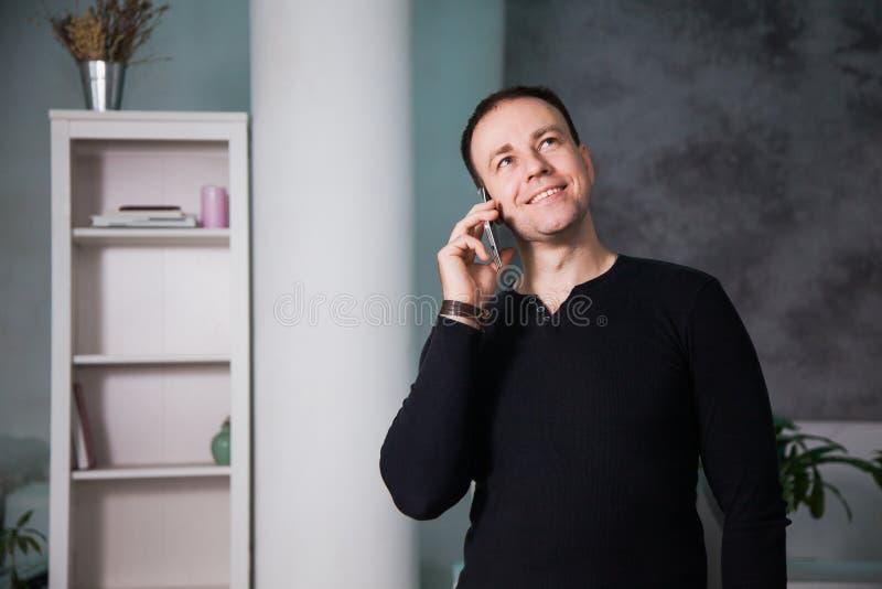 Homme heureux parlant par le téléphone au bureau photo stock