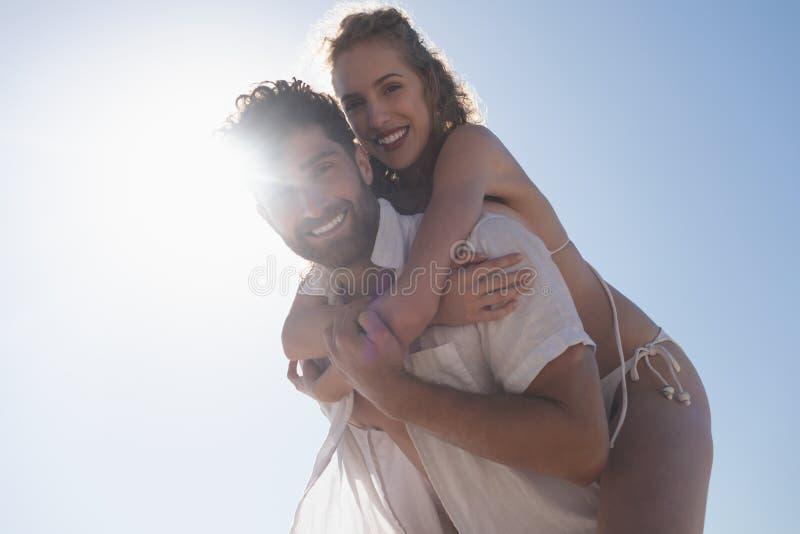 Homme heureux portant le joli ferroutage de femme à la plage images libres de droits