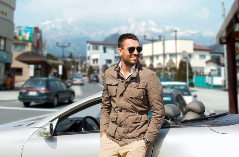 Homme heureux près de voiture de cabriolet au-dessus de ville au Japon image stock