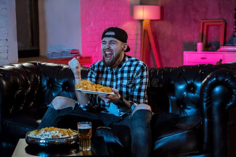 Homme heureux regardant la TV et l'encourageant la nuit photos stock