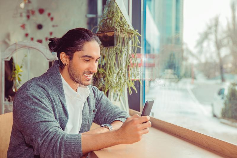 Homme heureux regardant le téléphone souriant, service de mini-messages photos libres de droits