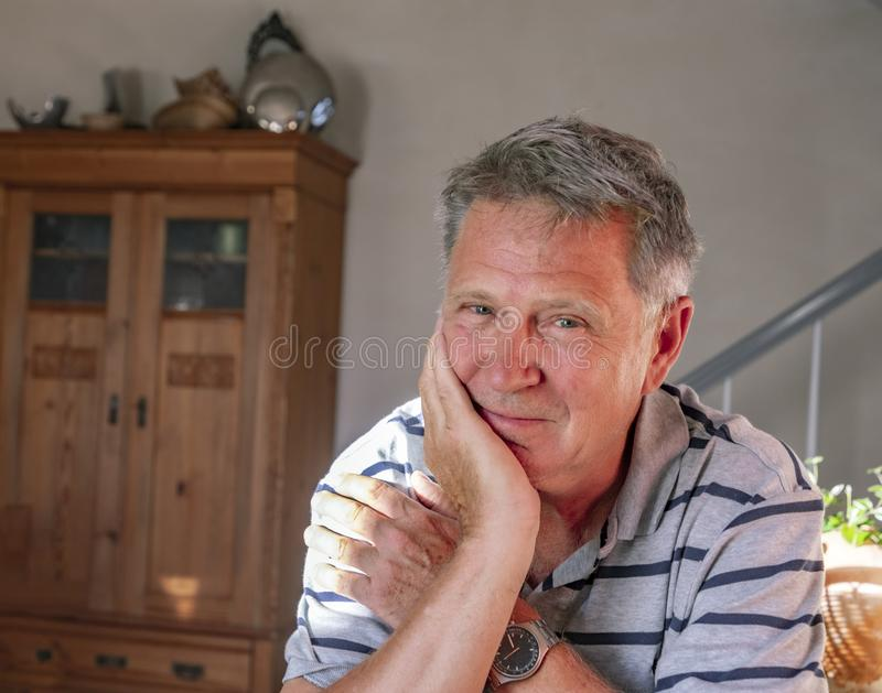 Homme heureux s'asseyant à la maison à la table et aux sourires photos stock