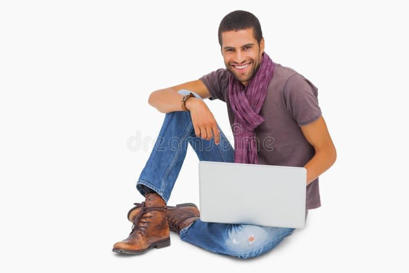 Homme heureux s'asseyant sur le plancher utilisant l'ordinateur portable regardant l'appareil-photo photographie stock