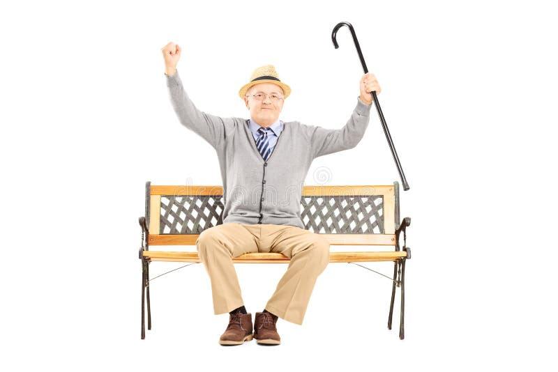 Homme heureux supérieur s'asseyant sur un banc et faisant des gestes le bonheur images libres de droits