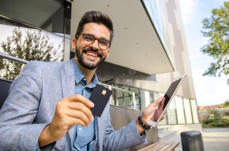 Homme heureux tenant le comprimé et la carte de crédit photographie stock