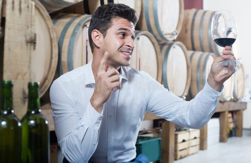 Homme heureux tenant le verre de vin rouge dans la boutique avec des bois photographie stock libre de droits