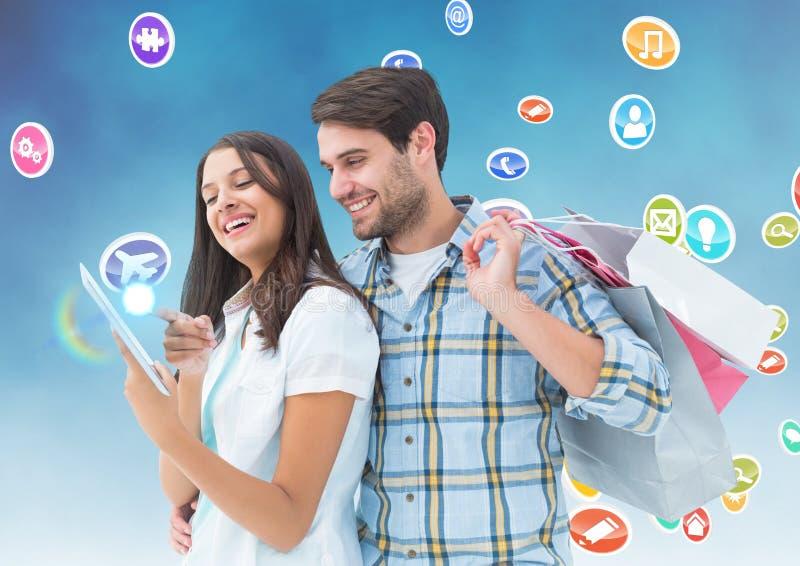 Homme heureux tenant les paniers et la femme à l'aide du comprimé numérique avec de diverses icônes à l'arrière-plan photo stock
