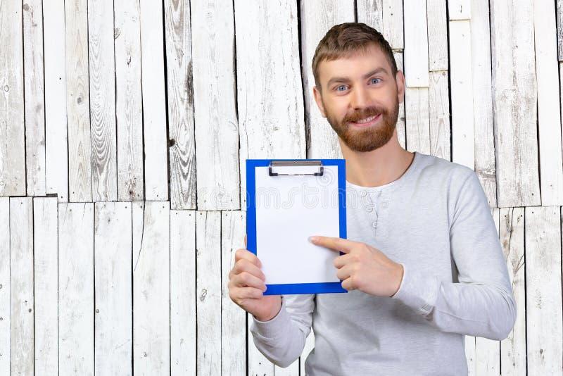Homme heureux tenant un presse-papiers photos stock