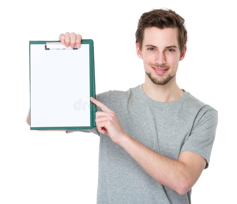 Homme heureux tenant un presse-papiers et se dirigeant avec un doigt photographie stock libre de droits