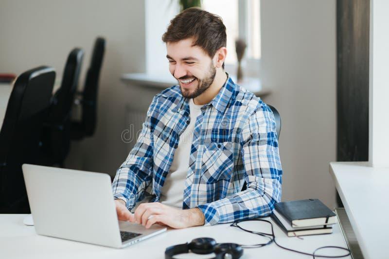 Homme heureux travaillant sur l'ordinateur portatif photographie stock libre de droits