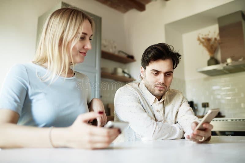 Homme hispanique attirant et femme blonde utilisant des téléphones portables à la maison image libre de droits