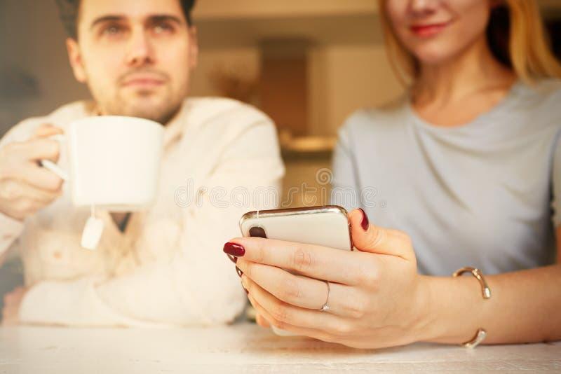 Homme hispanique attirant et femme blonde utilisant des téléphones portables à la maison photo libre de droits