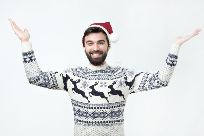Homme hispanique dans la position de chapeau de chandail et de Noël soulevant des mains dans la stupéfaction photographie stock