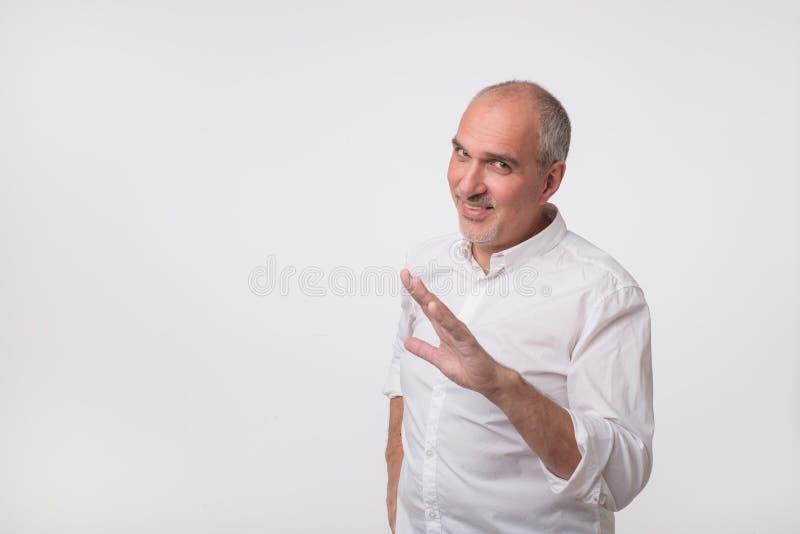 Homme hispanique mûr dans la chemise blanche montrant un geste comme l'arrêt svp, il est assez image libre de droits