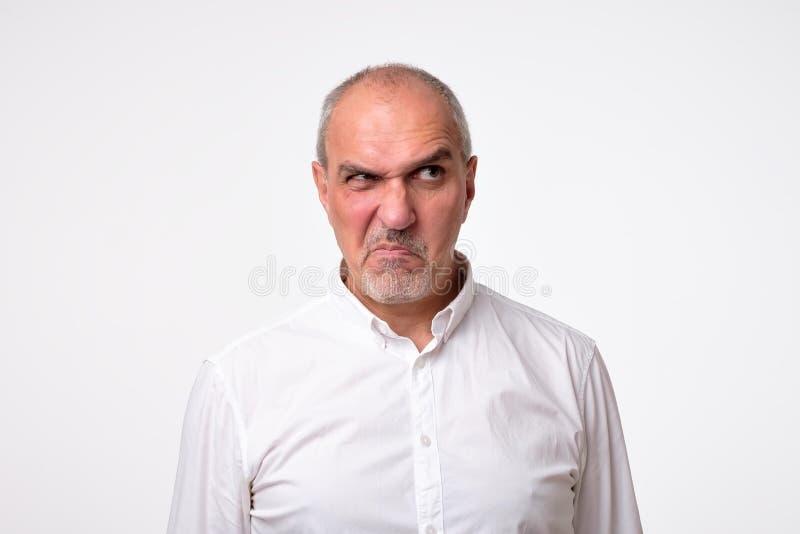 Homme hispanique mûr méfiant inquiété d'isolement sur le fond blanc de studio Son visage est dans la grimace de dégoût photographie stock libre de droits