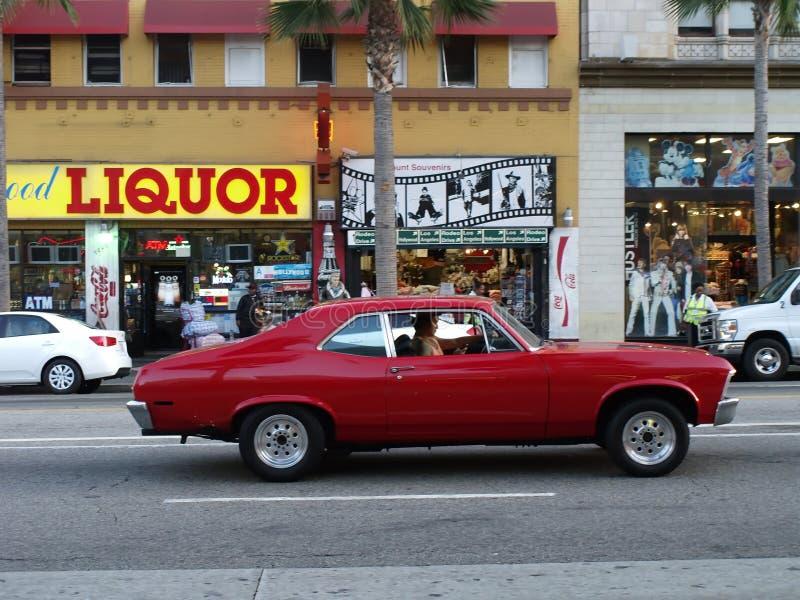 Homme hispanique non identifié conduisant une voiture rouge image libre de droits