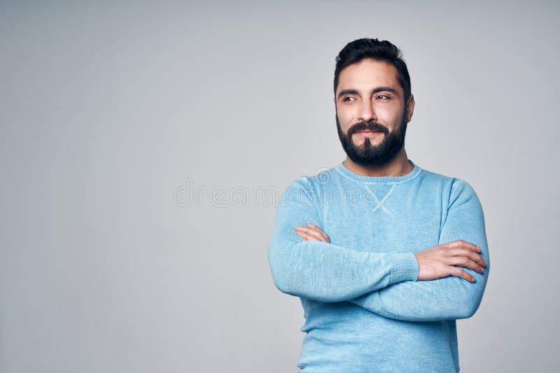 Homme hispanique s?r dans la position bleue de pull avec les mains pli?es image stock