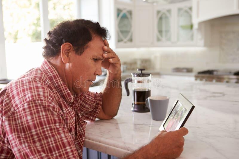 Homme hispanique supérieur à la maison regardant la vieille photographie image stock