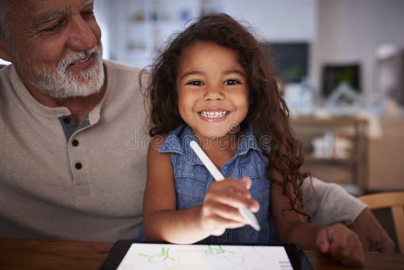 Homme hispanique supérieur avec sa jeune petite-fille à l'aide du stylet et de la tablette, souriant à la caméra photos libres de droits