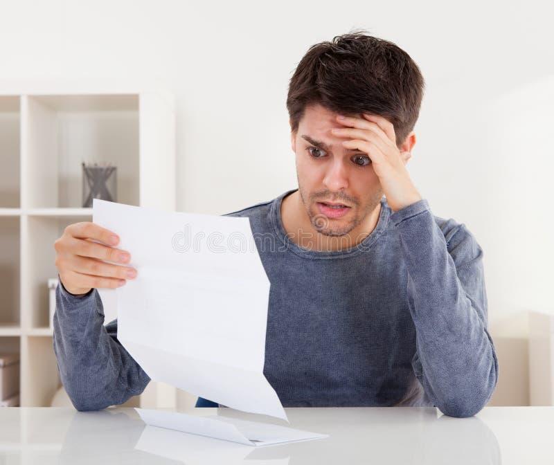 Homme horrifié lisant un document image stock