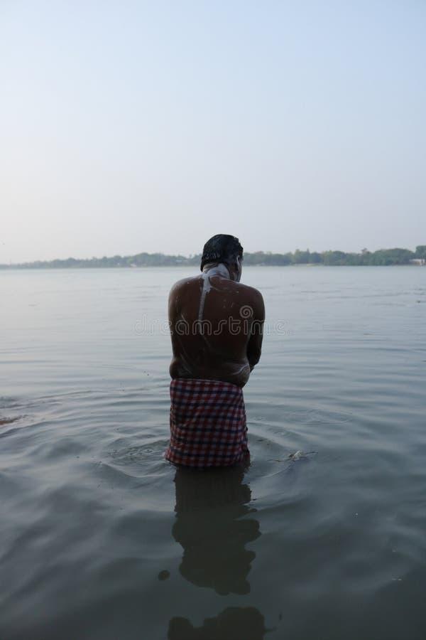 Homme inconnu se baignant en rivière Ganga en Inde photographie stock libre de droits