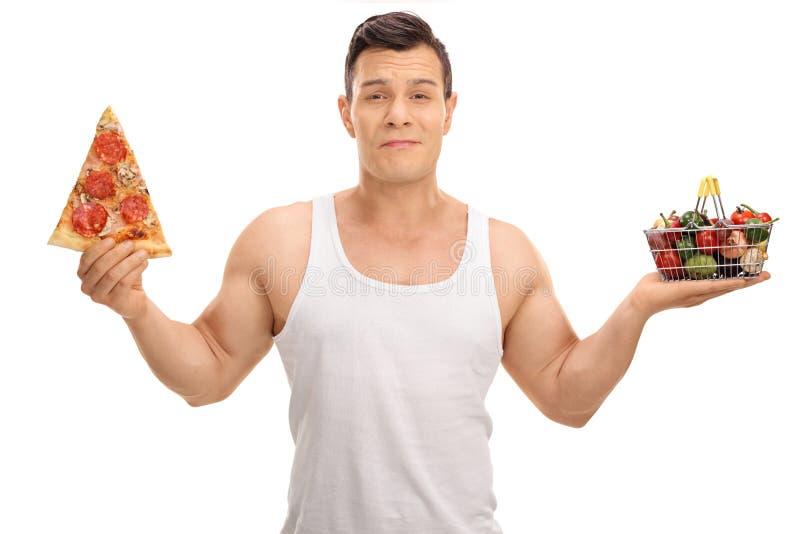 Homme indécis tenant le petits panier à provisions et tranche de pizza images libres de droits