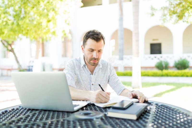 Homme indépendant préparant le programme dans le jardin image libre de droits