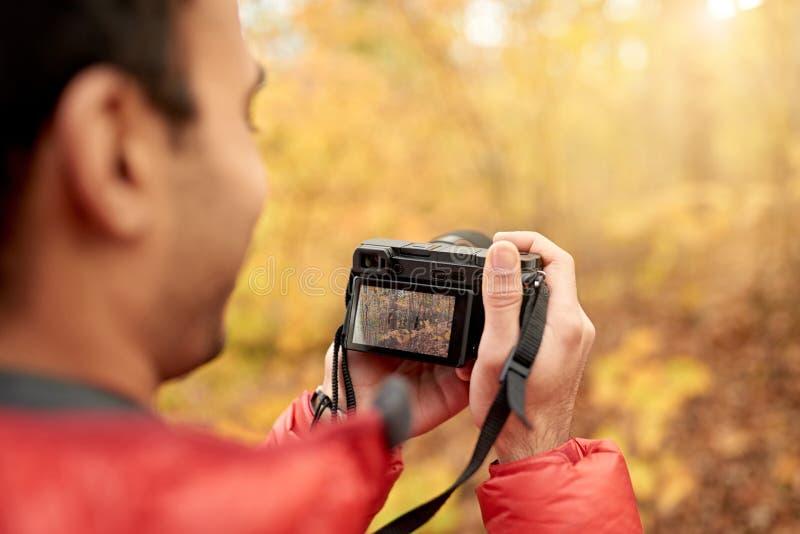Homme indien attirant prenant des photos avec une caméra mirrorless par la forêt en automne au Canada photographie stock libre de droits
