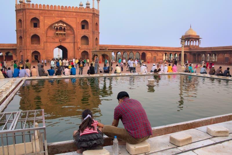 Homme indien avec une fille s'asseyant à la piscine en Jama Masjid dans Del photos stock